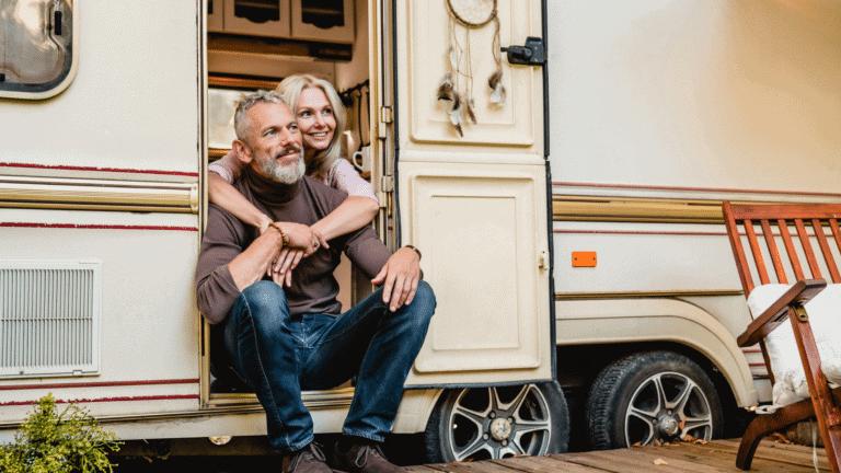 couple sitting in door of rv smiling