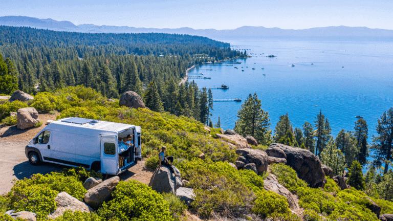 camper van parked overlooking blue water